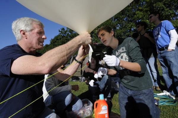 University of Maine electrical engineering professor Dr. Rick Eason (left) helps Bangor High School STEM Academy students craft a balloon tether release mechanism shortly before the launch of their weather research balloon at the high school Thursday morning, Sept. 27, 2012.