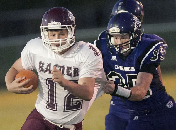 John Bapst's Riley Tapley (35) gets a grip on Washington Academy's Fred MacLean (12) in the first half of their game in Bangor, Maine, Sept. 15, 2012.