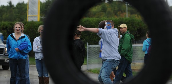 First-year student Bobby Ramsay attempts to throw a football through a tire as part of Maine's Black Bear Fanfair before the start of the Maine-Albany game at Orono on Saturday, September 22, 2012. A rock band played as fans sipped beer at the new beer garden.