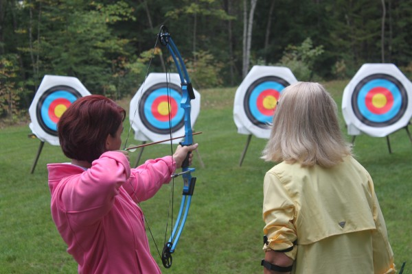 Sarah Ellis (left) learns how to shoot a compound bow from Mary Szwec, President of Friends of Maine BOW, on Sept. 15, 2012, during the Becoming an Outdoors-Woman (BOW) Introductory Skills Weekend at Camp Caribou in Winslow.