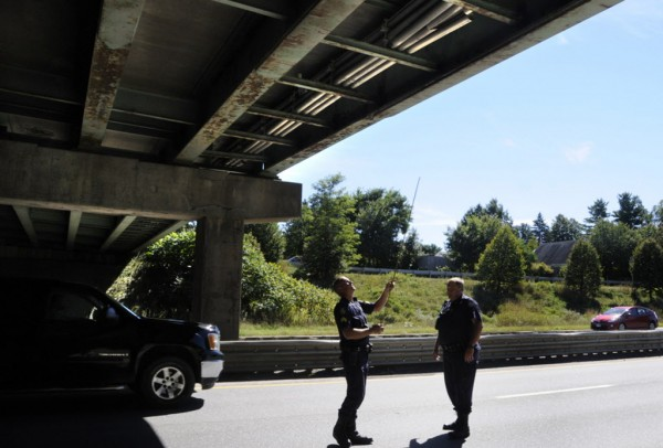 Maine State Police Sgt. Jason Sattler (left) and Trooper Phil Pushard use a tape measure to assess the structural damage to the Union Street bridge overpass after a truck's forklift and steel beam frame payload heading I-95-southbound failed to completely clear the overpass around 11:30 a.m. Thursday, Sept. 20, 2012.