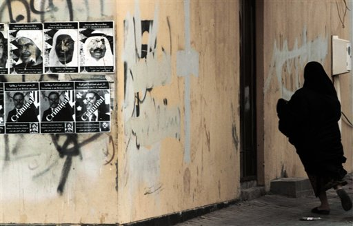 A Bahraini anti-government protester runs from riot police during clashes in Sitra, Bahrain, Monday, Sept. 3, 2012. Pictures of people killed in the unrest and of British Prime Minister David Cameron and U.S. President Barack Obama depicted as criminals for their close relations with the monarchy are plastered on the wall. Verdicts are expected Tuesday for numerous jailed leaders, medical workers and activists.