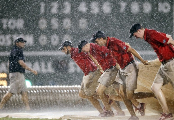 The Fenway Park grounds crew pulls out the tarp in heavy rain in the fourth inning of a baseball game between the Boston Red Sox and the Toronto Blue Jays in Boston, Saturday, Sept. 8, 2012.