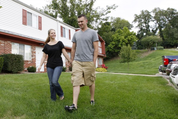 In this Monday, Aug. 20, 2012 photo, Marine Sgt. Ron Strang, right, walks with his girlfriend, Monica Michna, in the yard by his home in Jefferson Hills, Pa., just south of Pittsburgh. In 2008, the federal government created AFIRM, the Armed Forces Institute of Regenerative Medicine, a network of top hospitals and universities around the country, and gave $300 million in grants to spur new treatments using cell science and advanced plastic surgery. Strang is among those benefiting. The 28-year-old former Marine sergeant from Pittsburgh lost half of his left thigh muscle to shrapnel, leaving too little to stabilize his gait. &quotMy knee would buckle and I'd fall over,&quot he said. Now, after an experimental cell treatment at the University of Pittsburgh Medical Center, &quotI'm able to run a little bit&quot and play a light football game with friends, he said. &quotIt's been a huge improvement.&quot