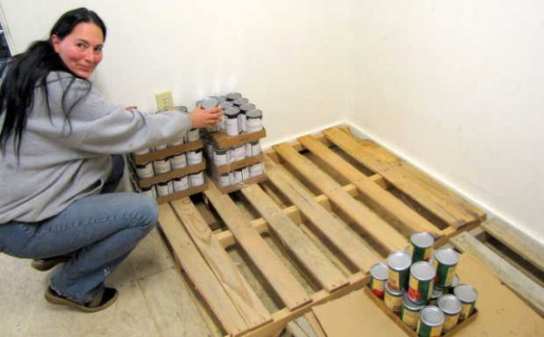 Kitty Green, a volunteer at Care and Share Food Closet in Farmington, selects cans of food from the dwindling supply.