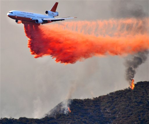 In this Sunday, Sept. 2, 2012 photo, a DC-10 tanker drops fire retardant on a ridge line at fire above East Fork Rd. near Glendora, Calif., in the Angeles National Forest. The wildfire has cut short the Labor Day holiday weekend for thousands of visitors who flock to the popular recreational attraction. The fire broke out near a campground Sunday afternoon and quickly grew to 3,600 acres, or about 5½ square miles. It sent a huge cloud of smoke that could be seen from the coast to the desert inland.