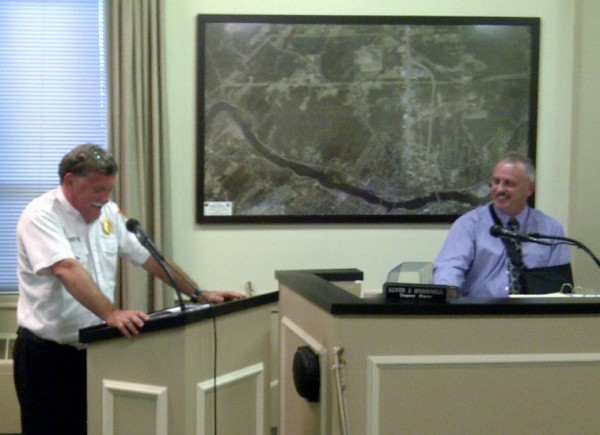 Fire Chief Gary Parent (left) turns red and holds onto the lectern while reading a fake City Council resolve on Sept. 11, 2012 that jokes about his 27 years with the Brewer Fire Department. Parent is retiring at the end of the month.