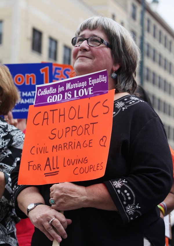 Kathy Tosney holds a sign as she listens to speakers Monday, Sept. 10, 2012 at a rally outside of City Hall in Portland in support of a ballot question that seeks to legalize same-sex marriage.