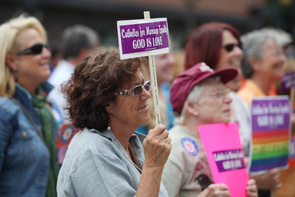 Cynthia Murray-Beliveau holds a sign as she listens to speakers Monday, Sept. 10, 2012 at a rally outside of City Hall in Portland in support of a ballot question that seeks to legalize same-sex marriage.