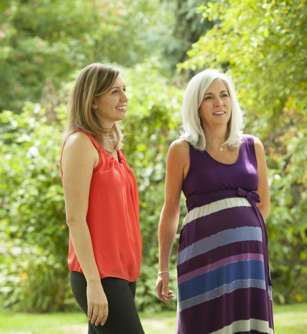 Emily Jordan, left, and her pregnant mother Cindy Reutzel relax at Jordan's home on Sunday, Aug. 19, 2012 in Naperville, Ill. After Jordan underwent a radical hysterectomy, she and her husband took up an offer from Reutzel to act as their surrogate.