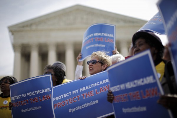 In this March 28, 2012 file photo, supporters of health care reform rally in front of the Supreme Court in Washington on the final day of arguments regarding the health care law signed by President Barack Obama. Congressional budget analysts are now estimating that nearly 6 million Americans, most of them in the middle class, will have to pay a tax penalty for not getting health insurance once Obama's health care law is fully in place. That's 2 million more than a previous estimate found, or a 50 percent increase.