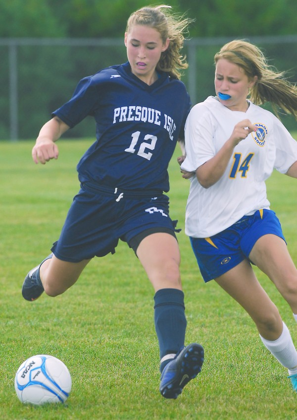 Presque Isle's Hannah Graham (12) is pressured by Hermon's Savannah Allain (14) as she tries to pass the ball in second-half action at Hermon High School, Saturday, Sept. 8, 2012.