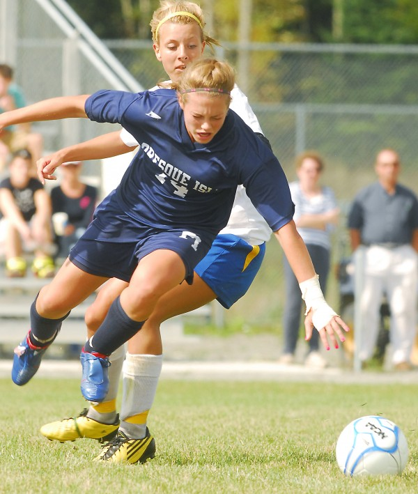 Presque Isle's Chandler Guerrette (14) leaves the ground after getting tangled up with Hermon's Gabby Bryant (10) as they struggled for control of the ball during second-half action at Hermon High School, Saturday, Sept. 8 2012.