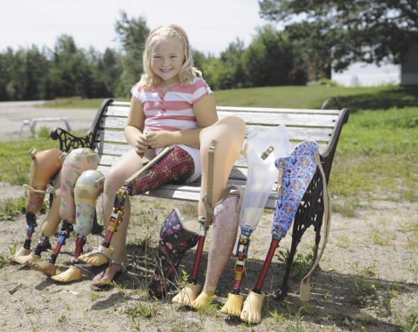 Jenna Colson, 7, of Birch Harbor poses with her collection of prosthetic legs, including one in her hands from when she was a baby. Colson was three months old when she had her leg amputated because of a medical condition. She was sponsored by a Shriner and was able to utilize the Shrine hospital where she continues to receive medical care for no out-of-pocket cost.