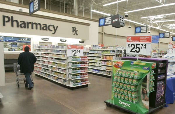 In this Feb. 20, 2008, file photo, a shopper walks toward the pharmacy at a Little Rock, Ark., Wal-Mart store. A study says seniors in seven of the 10 most popular Medicare prescription drug plans will be hit with double-digit premium hikes next year if they don't shop for a better deal. The report by Avalere Health is a reality check against the Obama's administration's upbeat pronouncements. Back in August 2012, officials had announced that the average premium for basic prescription drug coverage would stay the same in 2013, at $30 a month.