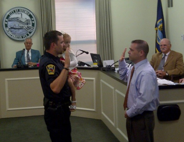 New Brewer police Officer Tom Tardiff holds his daughter while he is sworn in during the Brewer City Council meeting held Tuesday, Sept. 11, 2012 by City Clerk Howard Kroll.