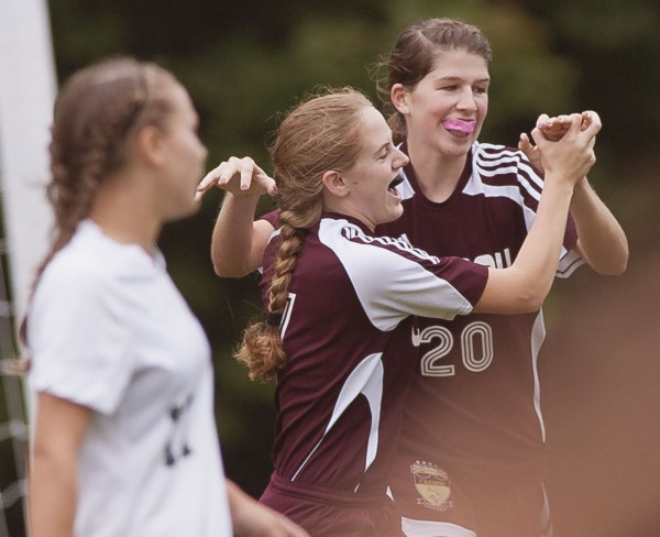 Caribou's Olivia Sleeper (left) and Sara Doak (20) celebrate their team's first-half goal in their game against Old Town in Old Town, Saturday, Sept. 22, 2012.