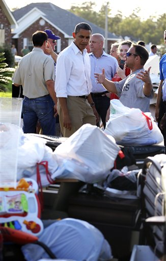 President Barack Obama, center, speaks with a local resident as he tours the Bridgewood neighborhood in LaPlace, La., in Saint John the Baptist Parish, as he surveys the ongoing response and recovery efforts to Hurricane Isaac, Monday, Sept. 3, 2012.