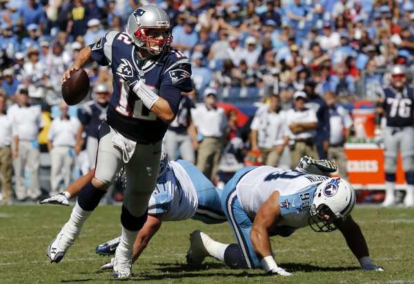 New England Patriots quarterback Tom Brady (12) scrambles away from Tennessee Titans' Mike Martin (93) and Karl Klug (97) in the fourth quarter of an NFL game, Sunday, Sept. 9, 2012, in Nashville, Tenn. The Patriots won 34-13.