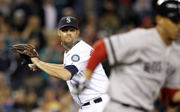 Seattle Mariners closer Tom Wilhelmsen, left, turns to throw to first on a grounder from Boston Red Sox Ivan De Jesus for the final out of a baseball game Wednesday, Sept. 5, 2012, in Seattle. The Mariners won 2-1.