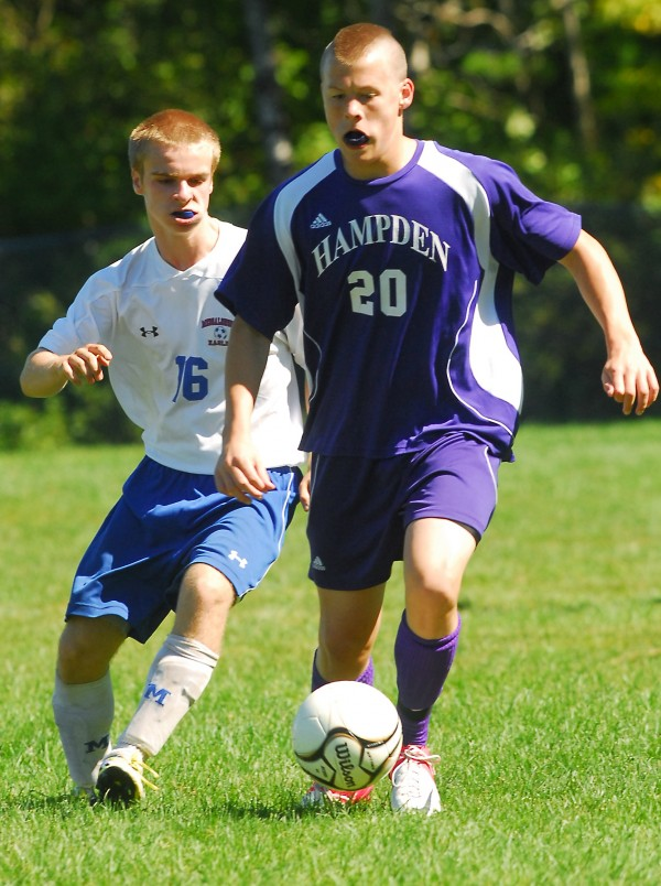 Hampden's Ben Foster (20) keeps ahead of Messalonskee's Peter Littlefield (16) during first-half action at Messalonskee High School Saturday, Sept. 1, 2012.