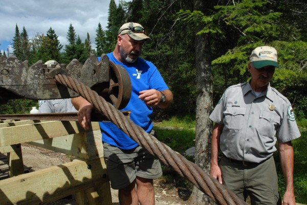 Steve Barnes (left) and Matthew LaRoche, supervisor of the Allagash Wilderness Waterway, look over the newly restored section of the old Allagash tramway. This past summer Barnes led a volunteer crew in refurbishing 25 feet of the 3,000-foot tramway.
