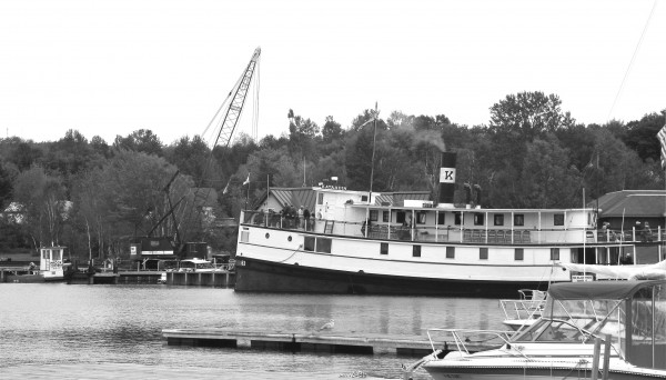 The SS Katahdin sails past a crane and a group of barges being assembled by Prock Marine Company to raise the Kate out of the waters of Moosehead Lake for needed repairs.