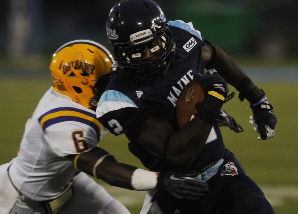 Maine's Maurice McDonald is brought down by Albany's Randall Exantus during first-quarter action at Orono on Saturday, Sept. 22, 2012.