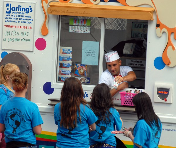 Jason Blackman hands out ice cream from the Darling's &quotIce Cream for a Cause&quot truck at the 2012 United Way of Eastern Maine's kickoff rally at Bass Park on Thursday.