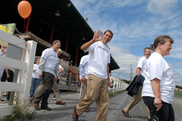 Jeff Spaulding with Eaton Peabody waves as he and his colleagues walk onto the racetrack at Bass Park for a parade that kicked off the United Way of Eastern Maine's 2012 campaign on Thursday.
