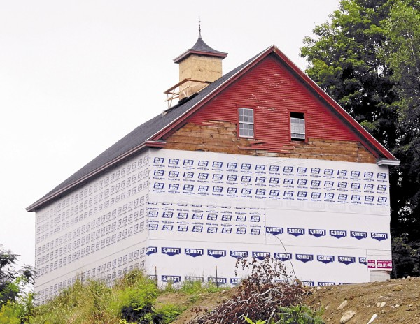 Local contractors are rebuilding the landmark barn that stands on a hill south of Winterport. In late August, the barn was enveloped in house wrap.