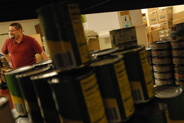 Seen through a  food cupboard shelf lined with canned goods, Paul Jerome talks with the BDN at the Brewer Christian Food Bank on Wednesday, Sept. 29, 2010.