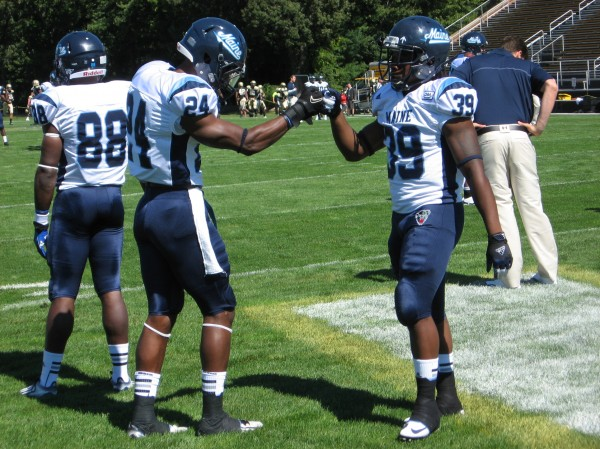 University of Maine teammates Khari Al-Mateen (left) and Rickey Stevens share a fist bump while warming up for Saturday's game against Bryant University in Smithfield, R.I. Al-Mateen returned an interception 77 yards for a touchdown and Stevens rushed for 168 yards in the Black Bears' 51-7 victory.
