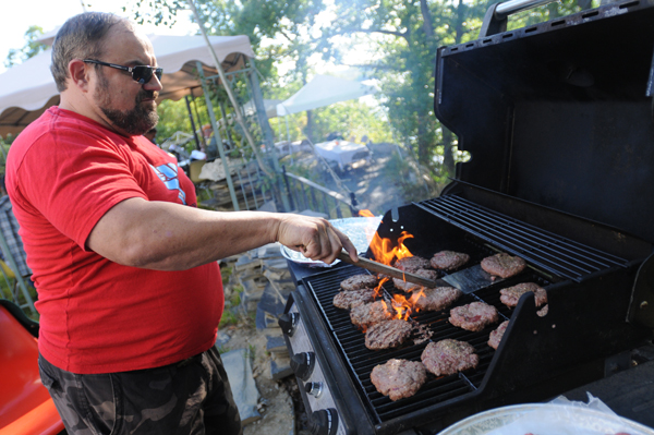 Randy Tompkins mans the grill while cooking organic burgers at the 10th annual Food AND Medicine Labor Day Celebration in Brewer on Monday, Sept. 3, 2012.