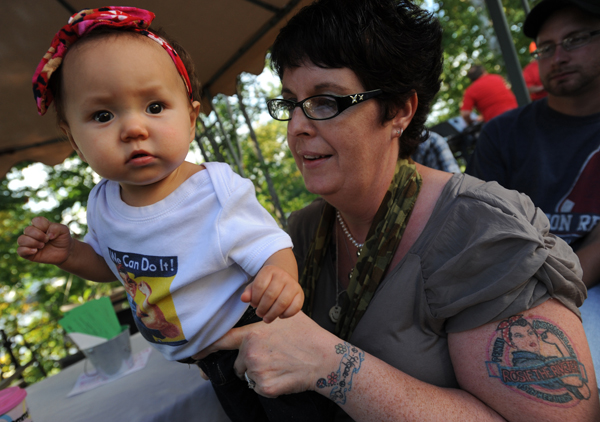 Zoe Dana sports a Rosie the Riveter shirt and bandana as she is held by her foster mother Penny Theriault of Princeton at the 10th annual Food AND Medicine Labor Day Celebration in Brewer on Monday, Sept. 3, 2012. The pair along with Theriault's husband and son were waiting for food to be served.