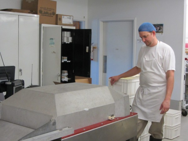 Cheesemaker David Baker operates a machine that seals the cheeses in packaging. State of Maine Cheese is located on Route 1 in Rockport.