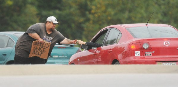 A man holding a sign indicating he is homeless accepts money from a motorist along Stillwater Ave in Bangor on Wednesday, Sept. 5, 2012.
