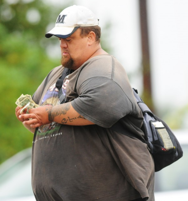 A panhandler counts a wad of cash he has accepted from passing motorist on Stillwater Ave. in Bangor on Wednesday, Sept. 5, 2012.