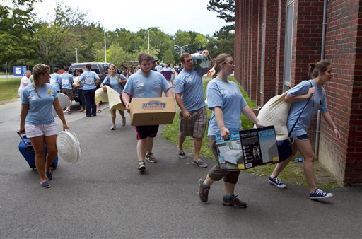 Blue-shirted upperclassmen help move items belonging to incoming freshman at the University of Maine in Orono. Enrollment at Maine's universities has been dropping for years, but education officials say  the student population should level off this fall following efforts to stem the decline.