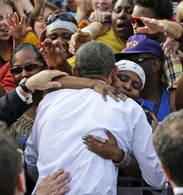 President Barack Obama is embraced by a unidentified supporter during a campaign event at Triangle Park in Dayton, Ohio, Tuesday, Oct. 23, 2012.