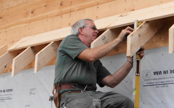 Richard Ames, lead carpenter on the Waldo County Habitat for Humanity house being built in Searsport, works on a trim detail.