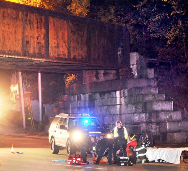 Emergency personnel tend to a man who was hit by a truck under the railroad trestle on Turner Street in Auburn on Friday night, Oct. 5, 2012.