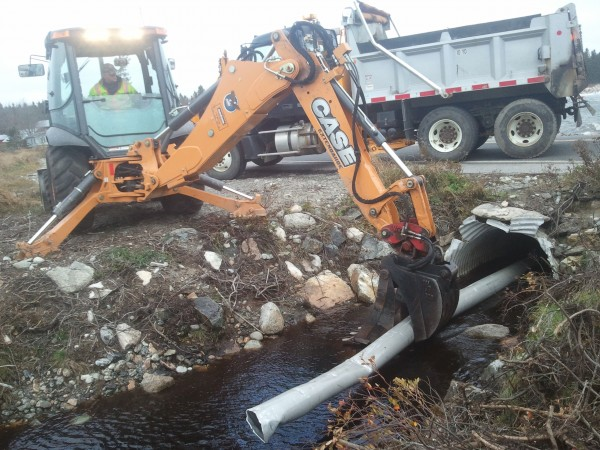 John Guiton, a Maine Department of Transportation worker, uses a section of pipe and a backhoe to clear a culvert under Route 102A at Seawall on Mount Desert Island on Monday, Oct. 29, 2012.