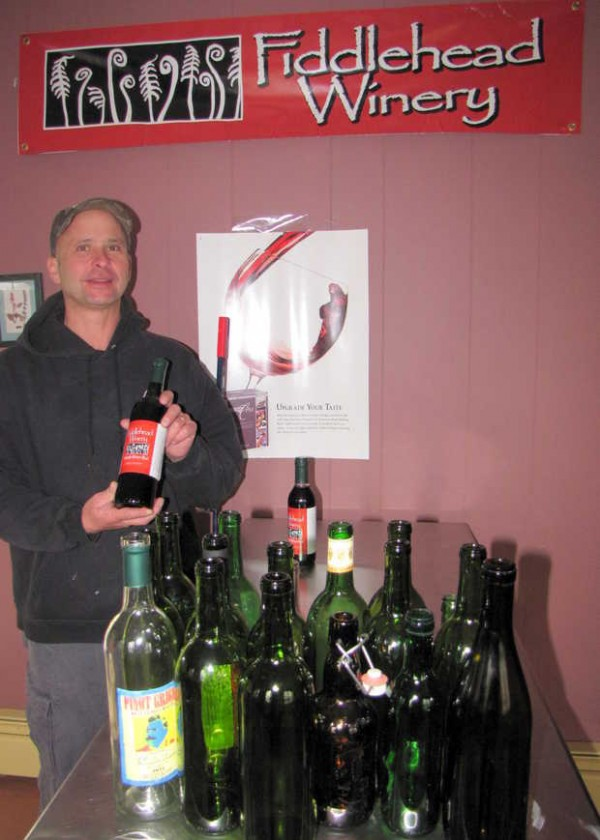 John Cormier holds a bottle of Sandy River Red, a wine produced in Farmington's new winery, Fiddlehead Winery.