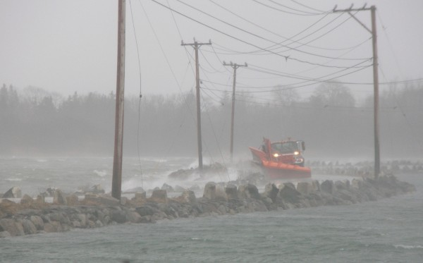 A DOT truck plows debris from the Deer Isle causeway deposited there by high winds that pummeled the Maine coast in April 2007.