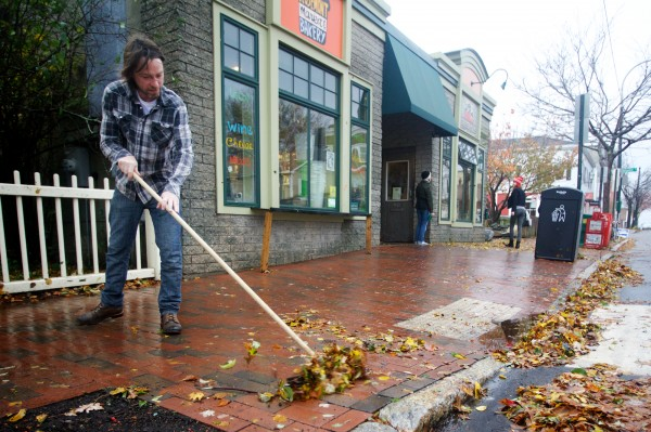 Joe Fournier sweeps leaves off the sidewalk in front of the Rosemont Market & Bakery on Munjoy Hill in Portland Tuesday morning, Oct. 30, 2012. Unlike farther south, Portland's storm damage was largely limited to downed limbs and power outages.