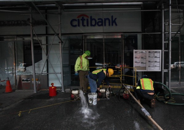 Workers pump water out of a flooded Citibank branch in New York's financial district Oct. 31, 2012. The U.S. Northeast began crawling back to normal on Wednesday after monster storm Sandy crippled transportation, knocked out power for millions and killed at least 45 people in nine states with a massive storm surge and rain that caused epic flooding.