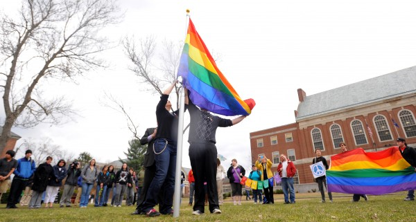 Rebecca Hickman (left) and Evan McDuff raise the Gay Pride flag in the front of the Fogler Library to mark the start of the annual Pride Week at the University of Maine in April 2012.