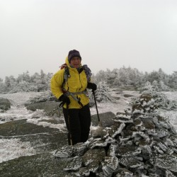 Jean Camuso, five peaks shy of completing all 67 of New England's 4,000-footers, stands at the almost-summit of Saddleback Mountain in a surprise October blizzard last week.