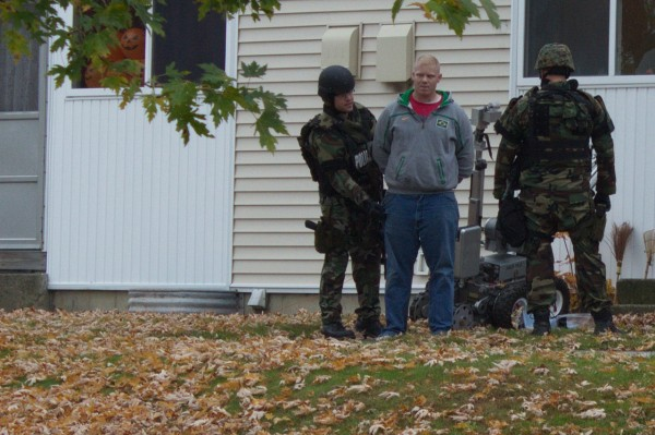 Jared Ross is taken into custody Friday in Bangor's Capehart neighborhood. Ross allegedly assaulted a woman while brandishing a shotgun just blocks from the Downeast School.